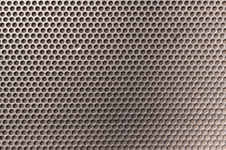 mesh: Metallic honeycomb hexagon grilled pattern in front of music speaker as background.