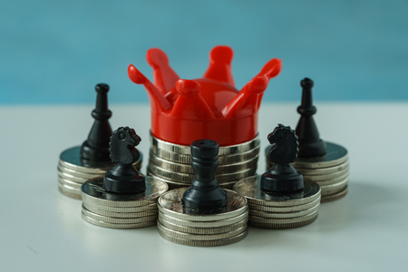 ganancias: Miniature red crown king on stack of coins and chess symbol as financial business growth success concept.
