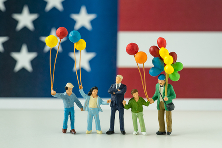 miniature figure, happy american family holding balloon with United State national flag in the background as celebrating the Independence day.