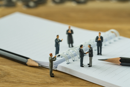 Miniature people, small figure businessman handshaking and others clapping on notebook and pencil as business agreement concept. Standard-Bild