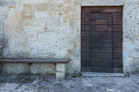 rivets: Aged vintage wooden door on stone building cave in Matera, south Italy. Stock Photo