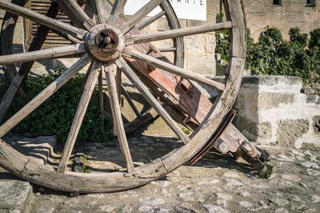 Vintage wood bullock wheel with sun shine summer, Matera Italy.