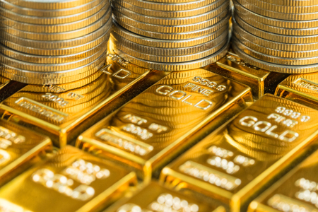 closed up shot of shiny gold bars with stack of coins as business or financial investment and wealth concept. Stock Photo