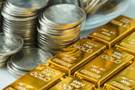 비즈니스 또는 금융 투자 및 부 개념으로 동전 스택과 반짝이 골드 막대.