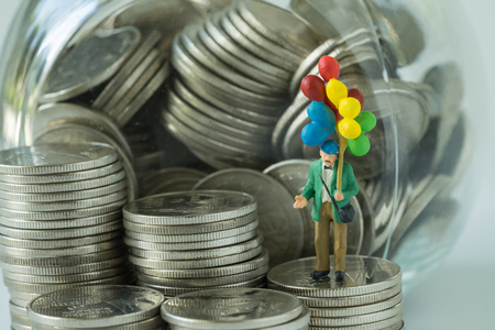 rate: Miniature figure old man holding balloon standing on coins, money in the jar as happy retirement saving concept.