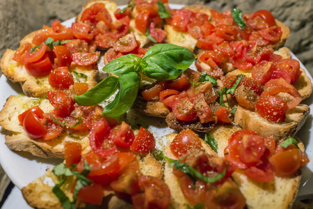 Italian bruschettas with chopped tomato and basil ready for breakfast.