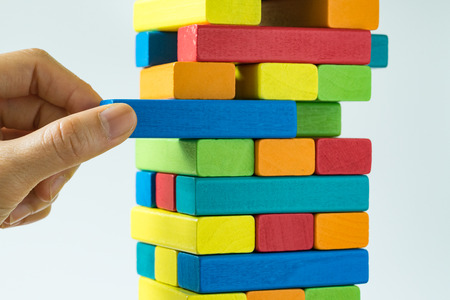 Hand pulling colorful wooden block from the tower in as Risk or stability concept.