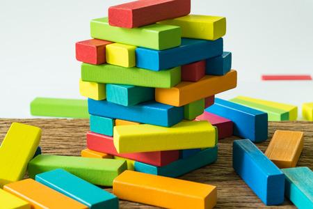 Fallire e collassare la torre di blocchi di legno colorata come concetto di rischio o di stabilità. Archivio Fotografico - 83941048