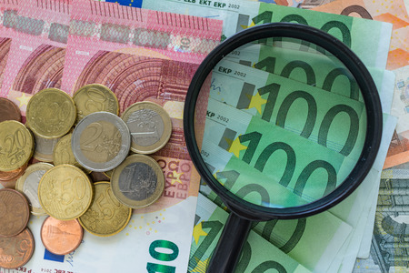 magnifying glass on pile of Euro banknotes with Euro coins as financial analysis concept. Banco de Imagens