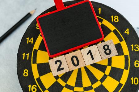 Jaar 2018 planningsdoelconcept met houten blokken nummer 2018 op dartboard met exemplaarruimte.