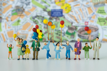 Miniature people with family holding balloons with map in the background as happy family or travel concept. Standard-Bild