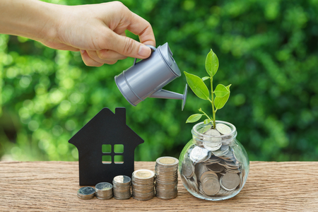 Stack of coins, paper house and growth sprout plant with hand watering as business finance or grow investment concept. Imagens