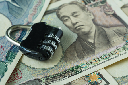selective focus on combination lockpad on pile of japanese yen banknotes as financial safe haven or security concept. Stock Photo