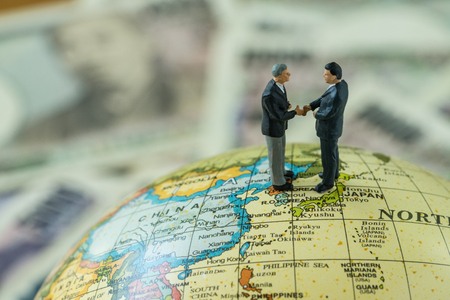 Miniature figure men handshaking standing on north korea and japan map globe as peace and war agreement nagotiation concept. Stock Photo