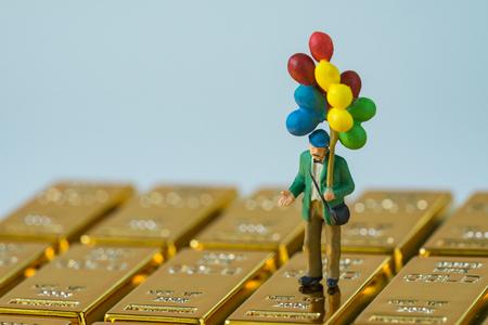 selectieve aandacht voor miniatuur figuur gelukkig man met ballonnen staande op glanzend goud bullions als financiële investering en veilige haven concept.