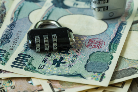 combination: selective focus on combination lockpad on pile of japanese yen banknotes as financial safe haven or security concept. Stock Photo