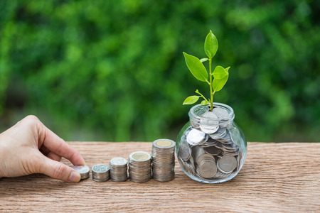 Hand holding stack of  coin and jar with growth sprout plant as financial investment concept. Stock Photo