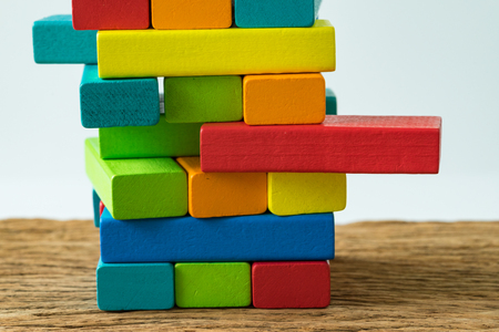 unstable colorful wooden block tower as Risk or stability concept. Archivio Fotografico