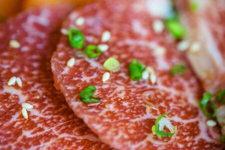 Selective focus on macro view of fresh A5 japanese supreme beef yakiniku cuisine with sesame and vegetable glaze.