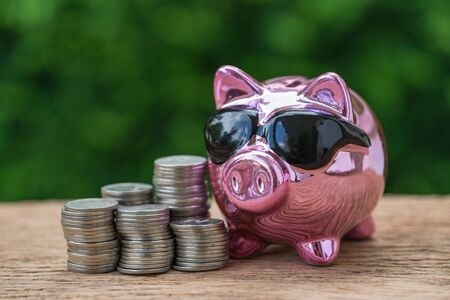 Selective focus on glossy pink piggy bank with stack of coins as saving or financial wealth concept.
