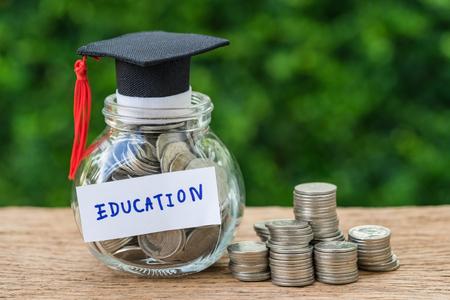 vaso di vetro con pieno di monete e laurea cappello etichetta come istruzione, educazione e pila di monete o concetto di risparmio.