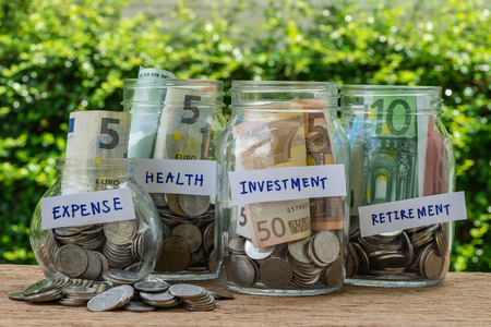 group of glass jar bottles with full of coins and banknotes labeled as expense, health,  investment and retirement as savings or investment concept.