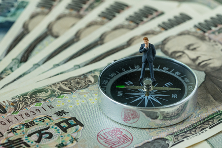 miniature figure businessman thinking standing on compass on pile of japanese yen banknotes as financial leader direction concept.