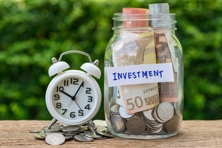 glass jar bottle labeled as investment with full of coins and banknotes, white alarm clock as savings or investment with timing goal concept.