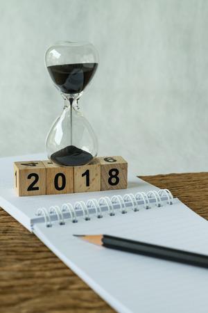 nieuw jaar 2018 doelen, doel of checklist concept als nummer 2018 houten kubus blok met zandloper en Witboek notitie met potlood op houten tafel. Stockfoto