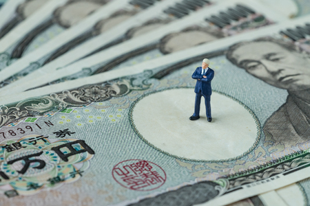 miniature figure businessman president or prime minister thinking standing on pile of japanese yen banknotes as financial economic leader concept.