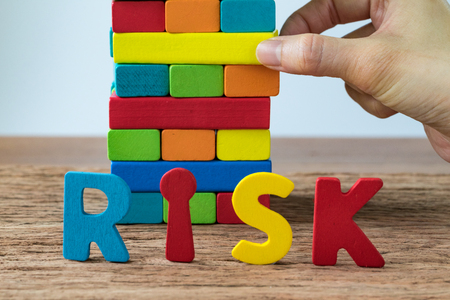derrumbe: business risk concept with hand pulling colorful wooden block tower with alphabets RISK.