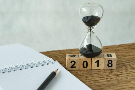 새 해 2018 목표, 번호 2018으로 대상 또는 검사 목록 개념 나무 테이블에 연필로 모래 시계와 백서 참고 나무 큐브 블록. 스톡 콘텐츠