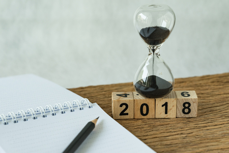 new year 2018 goals, target or checklist concept as number 2018 wooden cube block with sandglass and white paper note with pencil on wooden table. Фото со стока - 89361882