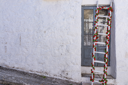 Decorated ladder with green and red flowers on vintage old white wall with copy space as starting Christmas holiday.
