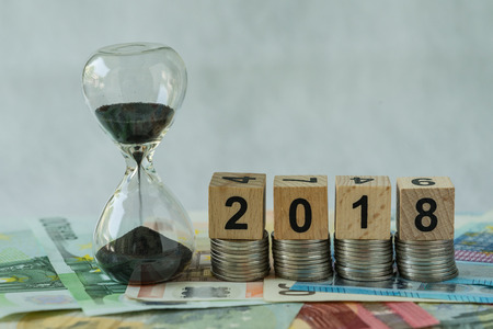 Year 2018 business time countdown or long term investment concept as hourglass or sandglass on pile of Euro banknotes with wooden cube block number 2018 on stack of coins.