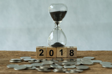 Year 2018 business time start or long term investment concept as hourglass or sandglass on wooden cube block number 2018 and coins on the wood table.