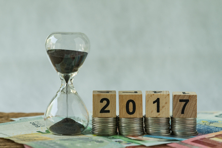 Year end 2017 business time countdown as hourglass or sandglass on pile of Euro banknotes with wooden cube block number 2017 on stack of coins.