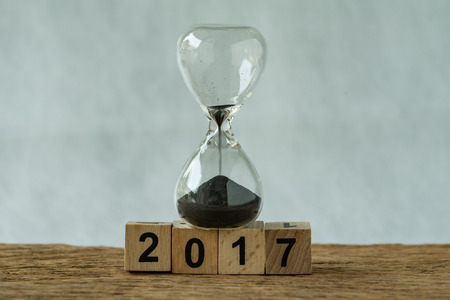 Year end 2017 business time countdown or improvement review concept as hourglass or sandglass with wooden cube block number 2017. Stock Photo