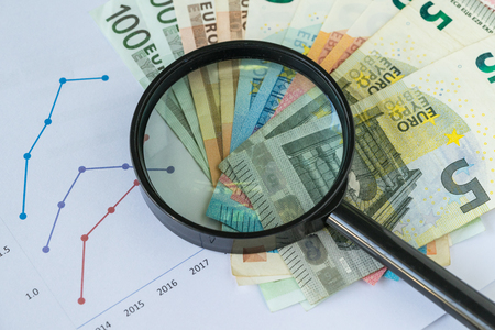 Magnifying glass on pile of Euro banknotes with printed bar chart and graph as Euro economy or debt analysis concept. Standard-Bild