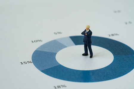 Miniature people with businessmen standing and thinking on printed analysis pie chart or graph as business yearly review or leadership concept. Stock Photo
