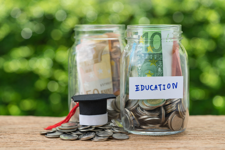 glass jar bottles with full of coins labeled as Education and graduates hat on stack of coins using as education or savings concept.
