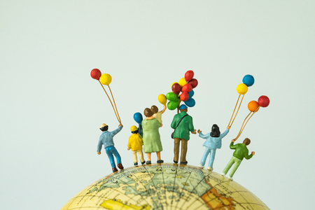 miniature people figure back view of happy family holding balloons standing on globe as looking into the universe or happy american family concept. Stock Photo
