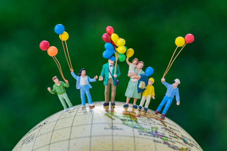 miniature people figure happy family holding balloons standing on united states of america map on globe as world climate change or happy family concept.