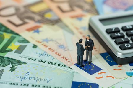 Miniaturzahl, die Geschäftsmänner, welche die Hand steht auf Stapel von Eurobanknoten mit Taschenrechner als Eurowirtschaftsvereinbarung oder Brexit-Verhandlungskonzept rütteln. Standard-Bild