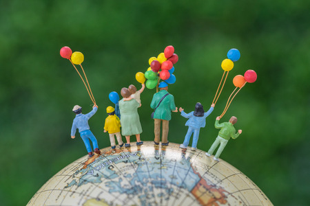 miniature people figure back view of happy family holding balloons standing on globe as world climate change environment or happy family concept. Stock Photo