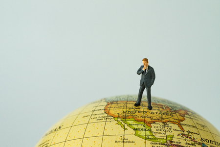 miniature people figure businessman president thinking and standing on united states of america map on globe as world leader decision concept.
