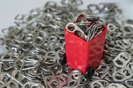 Red miniature bin with pile of hoop can opener or pull ring with red heart as recycle or consumer green world concept.