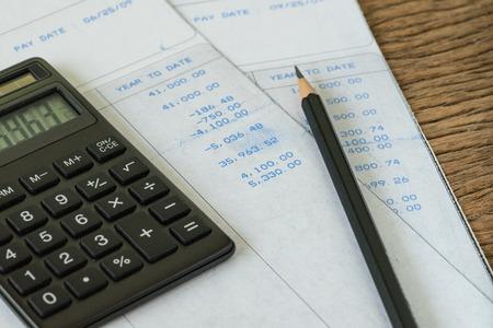 Homem do salário do escritório financeiro ou conceito do cálculo do imposto como a calculadora e o lápis pretos em deslizamentos de salário com números.