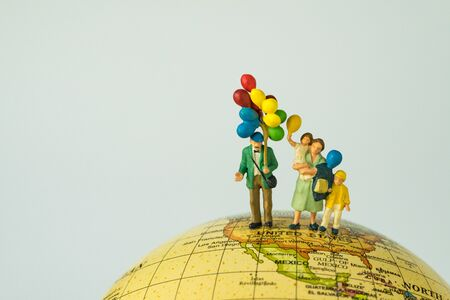 miniature people figure happy family holding balloons standing on united states of america map on globe as world climate change or happy american family concept.