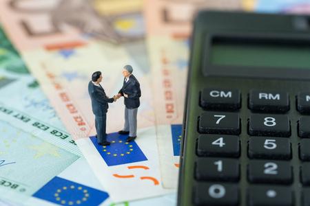 Miniaturowa figura, biznesmeni ściskający rękę stojącą na stosie banknotów euro z kalkulatorem jako umowa gospodarcza euro lub koncepcja negocjacji brexitu.